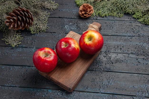 Widok z góry owoce na stole trzy jabłka na drewnianej desce do krojenia między gałęziami z szyszkami