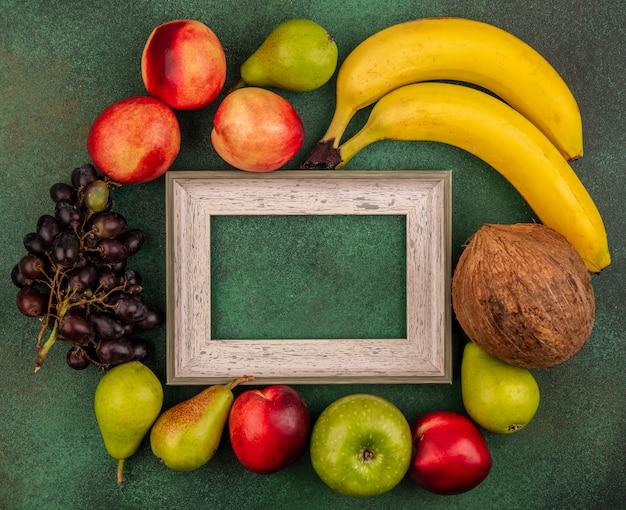 Widok z góry owoców jak brzoskwinia, kokos, jabłko, gruszka, banan, winogrona, wokół ramki na zielonym tle z miejsca na kopię