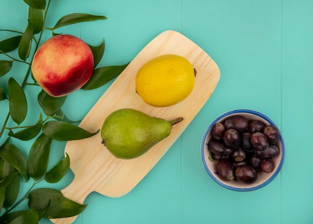 Widok z góry owoców jak cytryna gruszka na desce do krojenia i miska jagód winogron i brzoskwini z liśćmi na niebieskim tle