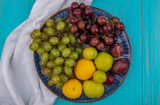 Widok z góry owoców jak pluots nectacots śliwki i winogrona w talerzu na białym obrusem na niebieskim tle