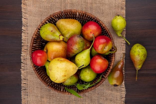 Widok z góry owoców jak śliwka brzoskwiniowo-jabłkowa w koszu i na worze na powierzchni drewnianych