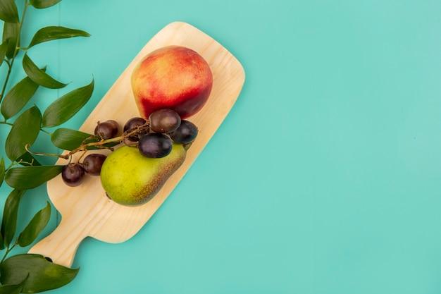 Widok z góry owoców jak winogrono brzoskwinia gruszka na deska do krojenia z liśćmi na niebieskim tle z miejsca na kopię