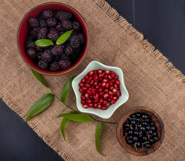 Widok z góry owoców jako granatu jeżynowego i jagód tarniny w miseczkach z liśćmi na worze na czarnej powierzchni