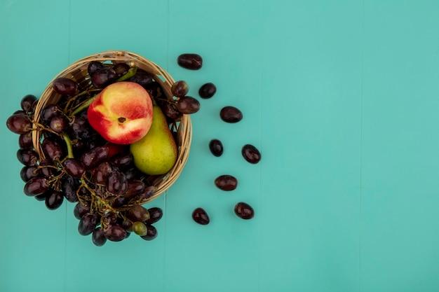 Widok z góry owoców jako kosz winogron i brzoskwiń z jagodami winogron na niebieskim tle z miejsca na kopię