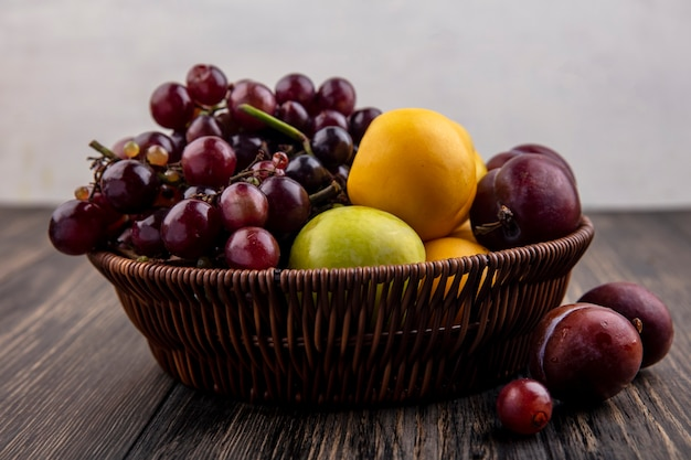 Widok z góry owoców jako nektakotów winogronowych w koszu i na powierzchni drewnianych i białym tle