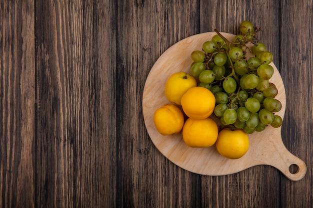 Widok z góry owoców jako nektakoty i białych winogron na deskę do krojenia na podłoże drewniane z miejsca na kopię