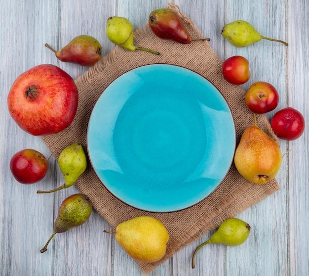 Widok z góry owoców jako śliwka brzoskwini granatu wokół pustego talerza na worze na drewnianej powierzchni