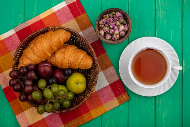 Widok z góry owoców jako winogron plukuje jagody tarniny z rogalikami w koszu na kraciastej tkaninie i miskę kwiatów z filiżanką herbaty na zielonym tle