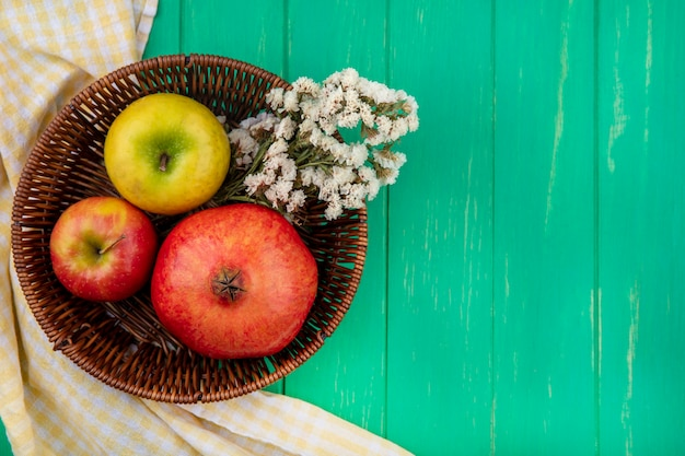 Widok z góry owoców, takich jak jabłko i granat z kwiatami w koszu na kraciastej tkaninie i zielonej powierzchni