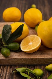Widok z góry owoców, takich jak kinkans i cytryny, na białym tle na drewnianej desce kuchennej na drewnianej ścianie