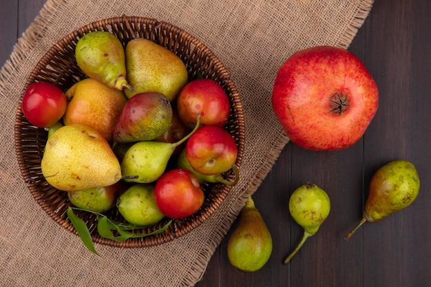 Widok z góry owoców w koszu z granatem na worze na drewnianej powierzchni