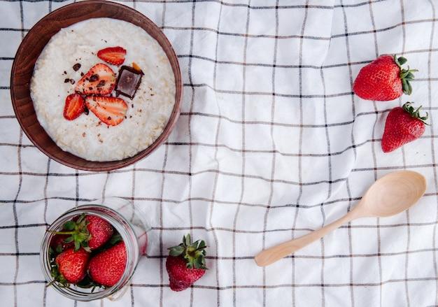 Widok z góry owsianki owsianej w misce ze świeżymi dojrzałymi truskawkami i drewnianą łyżką na kraciastej tkaninie z miejscem na kopię