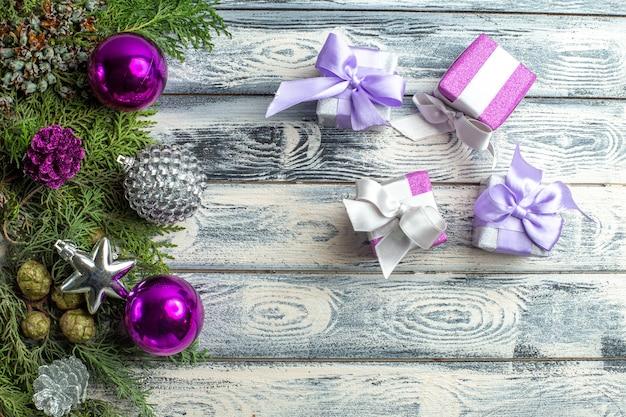 Widok z góry ozdoby świąteczne małe prezenty gałęzie jodły świąteczne zabawki na drewnianej powierzchni