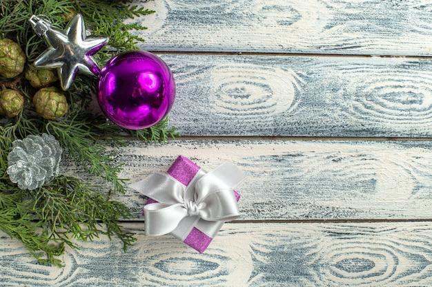 Widok z góry ozdoby świąteczne mały prezent gałęzie jodły świąteczne zabawki na drewnianej powierzchni