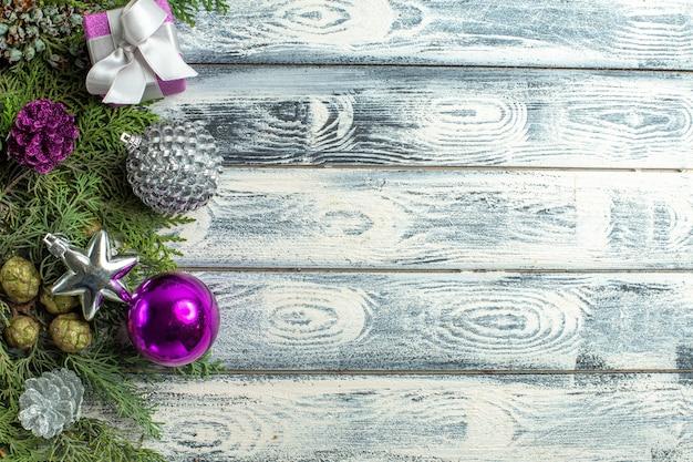 Widok z góry ozdoby świąteczne mały prezent gałęzie jodły świąteczne zabawki na drewnianym tle