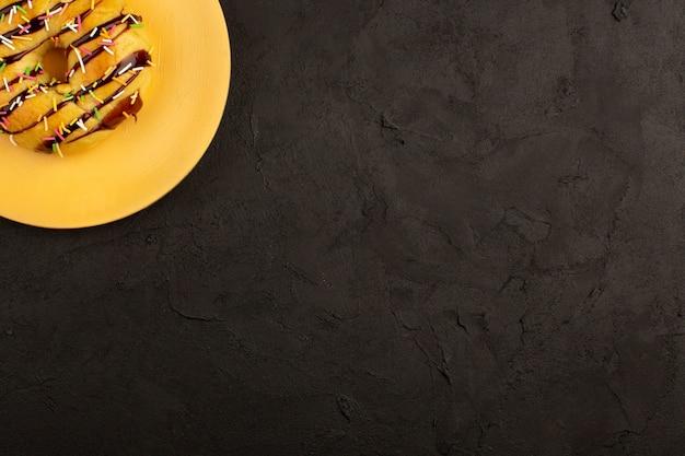 Widok z góry pączek zaprojektowany z kolorowymi cukierkami i czekoladą w pomarańczowym talerzu na ciemnym biurku