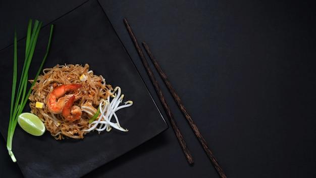 Widok z góry pad thai, wymieszaj muchę tajskiego kluski z krewetkami i jajkiem w czarnym talerzu ceramicznym na czarnym stole