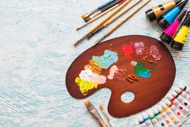 Widok z góry paleta farb w otoczeniu materiałów malarskich