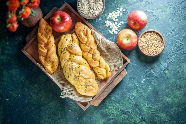Widok z góry paluszki chlebowe z dzianiny na prostokątnej desce z jabłek na wolnym miejscu na stole