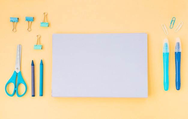 Widok z góry pamiętnika; kredki; nożyczki i spinacze ustawione na kolorowym papierze