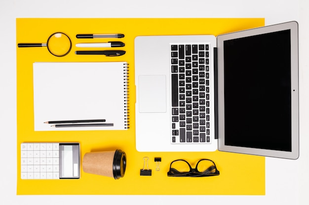Widok z góry papeterii z laptopem, notesami, lupą i kalkulatorem na żółtej powierzchni