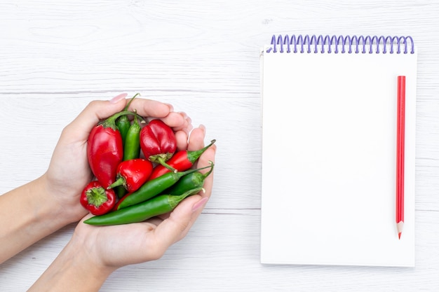 Widok z góry papryka ostra ostra trzymaj przez kobietę z notatnikiem na lekkim, warzywnym gorącym pikantnym posiłku surowym