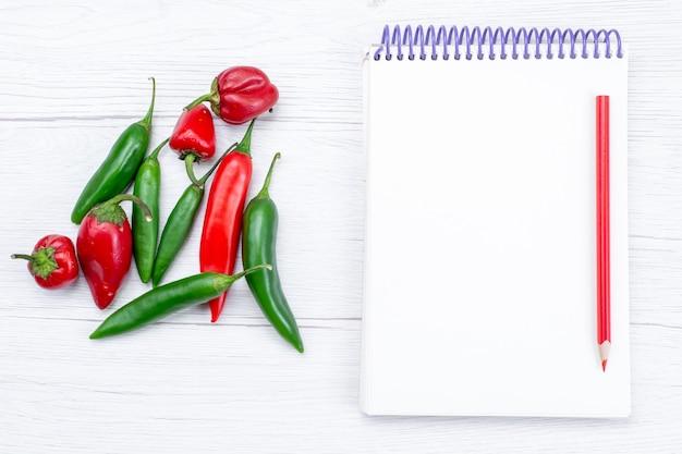 Widok z góry papryka ostra z notatnikiem na lekkim, warzywnym gorącym pikantnym posiłku na surowo