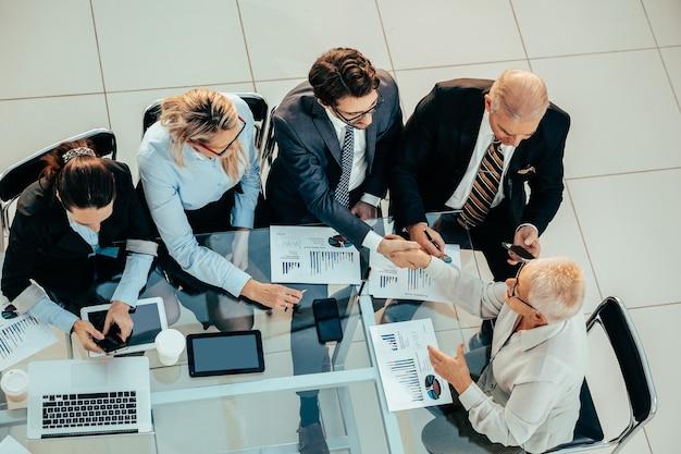 Widok z góry. partnerzy finansowi podają sobie ręce. pojęcie zgody.