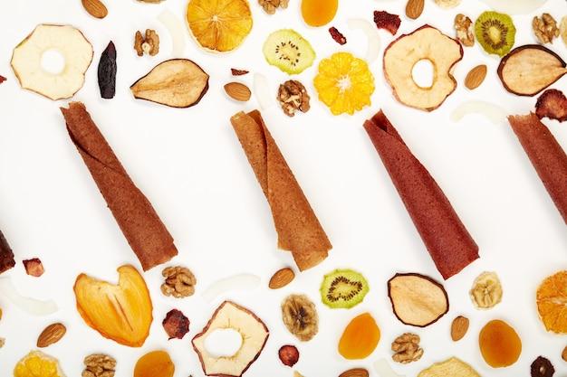 Widok z góry pastylek owocowych różnych kolorów i migdałów, pomarańczy, suszonej moreli, rodzynek, orzechów włoskich, suszonych jabłek i kiwi na białym