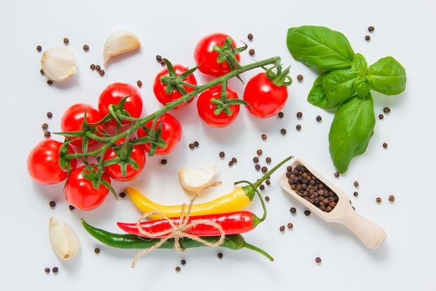 Widok z góry pęczek pomidorów z czarnym pieprzem, liście, czosnek, papryka chili na szarym tle. poziomy