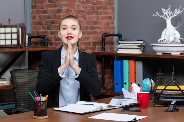 Widok z góry pełnej nadziei młodej kobiety siedzącej przy stole i trzymającej w biurze dokument z podziękowaniem