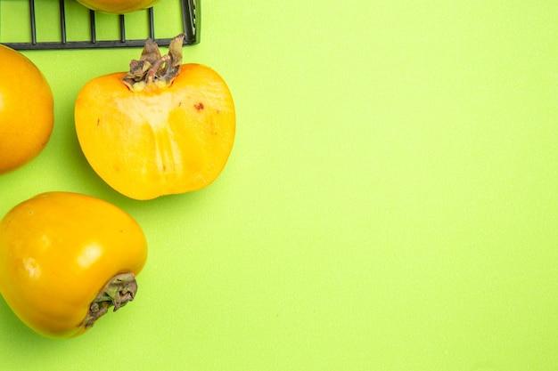 Widok z góry persimmons trzy persimmons obok szarego kosza na zielonym tle