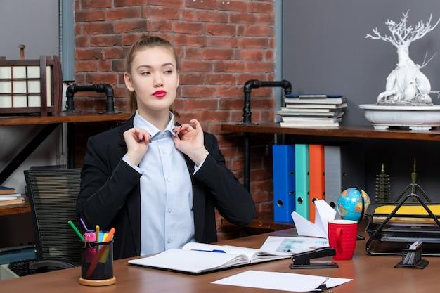Widok z góry pewnej siebie młodej kobiety siedzącej przy stole i skoncentrowanej na czymś w biurze