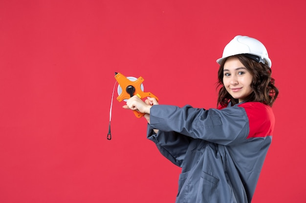 Widok z góry pewnie kobiecego architekta w mundurze z twardym kapeluszem trzymającym taśmę pomiarową na na białym tle czerwonym tle