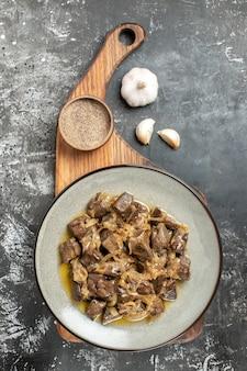 Widok z góry pieczona wątróbka i cebula na talerzu czarny pieprz na desce do krojenia czosnek na szarym stole