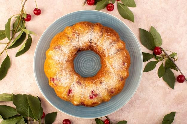 Widok z góry pieczone ciasto owocowe pyszne okrągłe z czerwonymi wiśniami w środku i cukrem pudrem wewnątrz okrągłego talerza na różowo