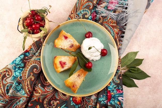 Widok z góry pieczone ciasto owocowe pyszne plastry z czerwonymi wiśniami w środku i cukrem pudrem w okrągłym zielonym talerzu