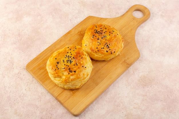 Widok z góry pieczone qogale w okrągłym kształcie smaczne gorące świeże z piekarnika na brązowym drewnianym biurku