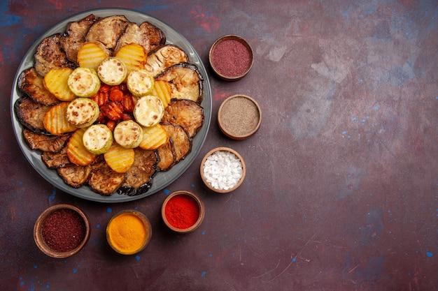 Widok z góry pieczone warzywa ziemniaki i bakłażany z przyprawami na ciemnej przestrzeni