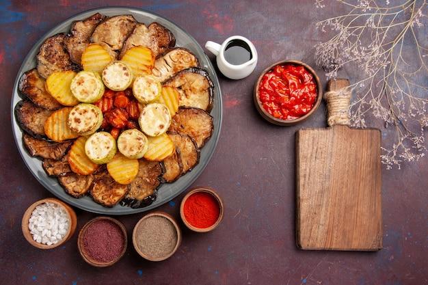 Widok z góry pieczone warzywa ziemniaki i bakłażany z różnymi przyprawami na ciemnym biurku