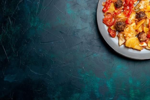 Widok z góry pieczone ziemniaki z klopsikami i warzywami wewnątrz płyty na ciemnoniebieskim tle.