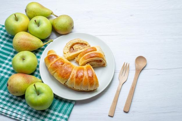 Widok z góry pieczonej bransoletki z pysznego ciasta uformowanej wewnątrz pokrojonego w szklanki talerza wraz z jabłkami i gruszkami na białym, słodkim ciasteczkowym ciastku