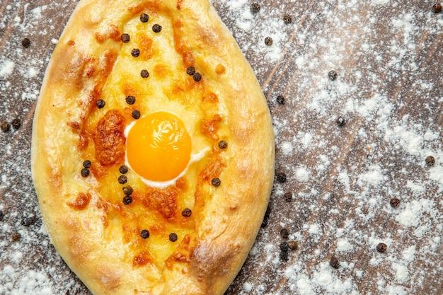 Widok z góry pieczony chleb z gotowanym jajkiem i mąką na brązowej powierzchni ciasto jajko chleb bułka śniadanie