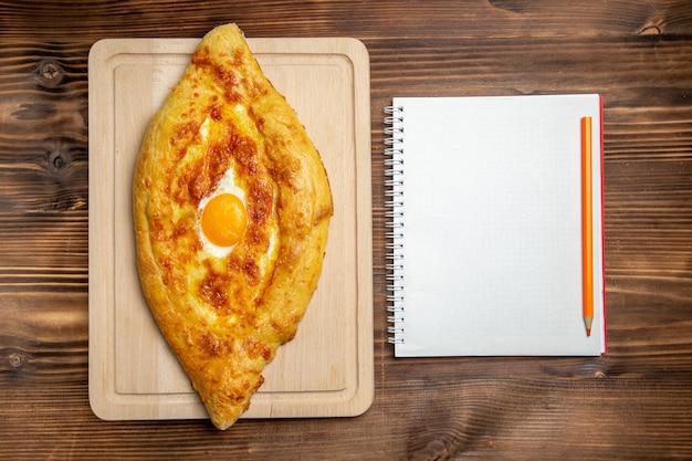Widok z góry pieczony chleb z gotowanym jajkiem na drewnianej powierzchni chleb ciasto bułka śniadanie żywności
