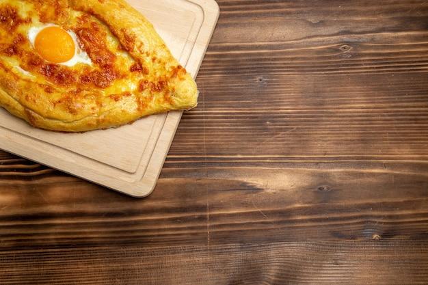 Widok z góry pieczony chleb z gotowanym jajkiem na drewnianym tle chleb bułka jedzenie jajka ciasto śniadaniowe