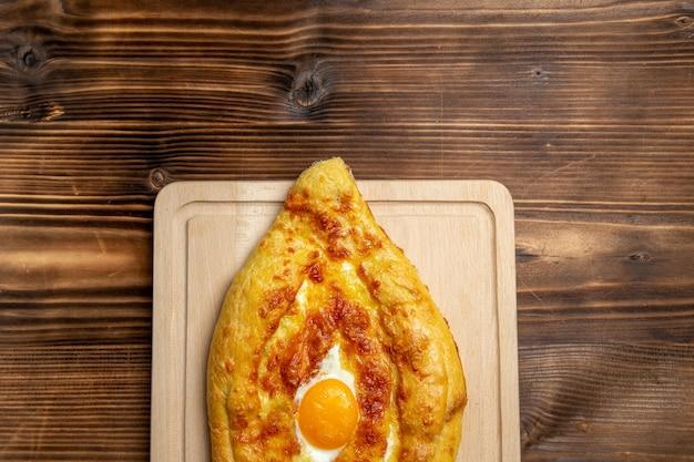 Widok z góry pieczony chleb z gotowanym jajkiem na powierzchni drewnianej chleb bułka jedzenie jajko ciasto śniadaniowe