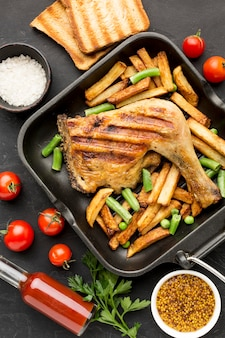 Widok z góry pieczony kurczak i ziemniaki na patelni z pomidorami i tostami