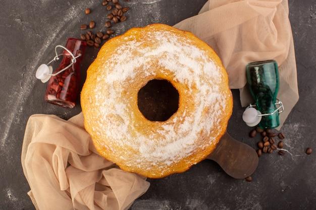 Widok z góry pieczony okrągły tort z cukrem pudrem i ziarnami kawy na drewnianym biurku