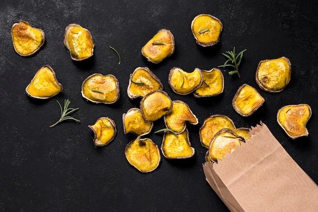 Widok z góry pieczonych ziemniaków z papierową torbą i rozmarynem