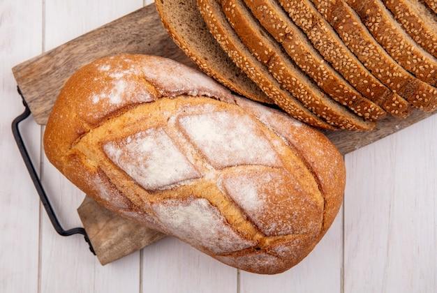 Widok z góry pieczywa jako pokrojone brązowe ziarno kolby i chrupiący chleb na deska do krojenia na drewniane tła